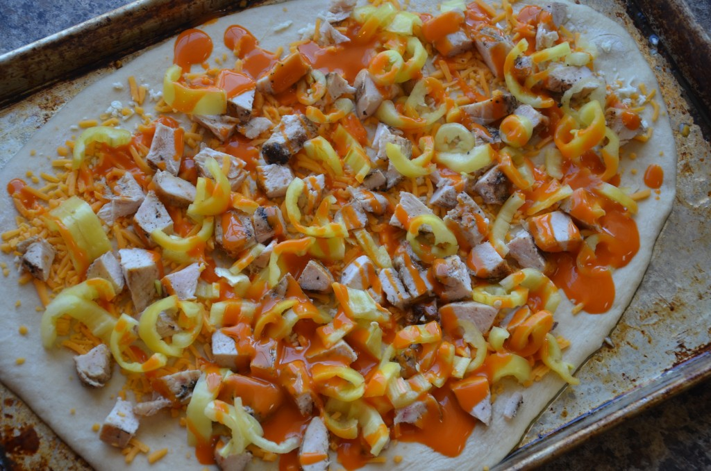 Pizza crust topped with cheddar cheese, chicken, peppers and buffalo sauce.
